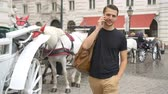 vídeň : Tourist man enjoying a stroll through Vienna and looking at the beautiful horses in the carriage