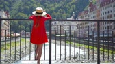 torre : Little girl at hat on the embankment of a mountain river in a European city.