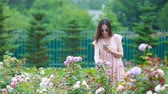 os olhos fechados : Young girl in a flower garden among beautiful roses. Smell of roses