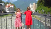 olympiáda : Back view of girls on the embankment of a mountain river in a European city.