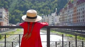 olympiáda : Little girl at hat on the embankment of a mountain river in a European city.