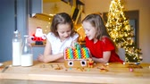 perník : Little girls making Christmas gingerbread house at fireplace in decorated living room.