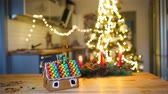 multicolorido : Gingerbread fairy house on a background of bright Christmas tree with garland