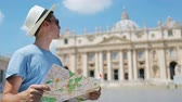 посещающий : Young man with city map in Vatican city and St. Peters Basilica church, Rome, Italy. Travel tourist man with map outdoors during holidays in Europe.