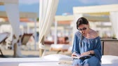 napágy : Young woman reading book during tropical beach vacation. Fashion girl read sitting in white sunbeds at european beach weekeend