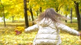 park : Portrait of adorable little girl with yellow leaves bouquet in fall Stock Footage