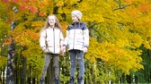 晴れた : Little adorable girls at warm day in autumn park outdoors