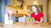 сочельник : Little girls making Christmas gingerbread house at fireplace in decorated living room.