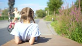 Little adorable girl listening music in the park Stock Footage