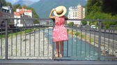 晴れた : Little girl at hat on the embankment of a mountain river in a European city.