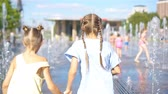晴れた : Little adorable girls have fun in street fountain at hot sunny day