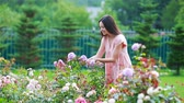 Young girl in a flower garden among beautiful roses. Smell of roses