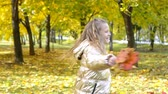 晴れた : Portrait of adorable little girl with yellow leaves bouquet in fall 動画素材
