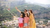 четыре человека : Parents and kids taking selfie photo background Positano town in Itali on Amalfi coast