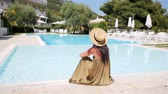 warme kleidung : Woman relaxing by the pool in a luxury hotel resort enjoying perfect beach holiday vacation