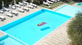 suntan : Young woman in bikini air mattress in the big swimming pool