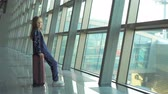 boarding pass : Adorable little girl in airport near big window playing with her phone Stock Footage