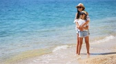 Beautiful mother and daughter at Caribbean beach enjoying summer vacation. Dostupné videozáznamy