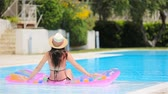 Young woman in bikini air mattress in the big swimming pool