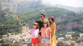 Parents and kids taking selfie photo background Positano town in Itali on Amalfi coast