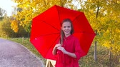 chovendo : Happy child girl laughs under red umbrella Stock Footage