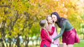 Family of mom and kids in fall. Young mother and little girls enjoy warm autumn Dostupné videozáznamy