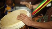 African Percussion - Traditional music. Closeup of mans hands drumming out a beat on an African skin-covered djembe hand drum.