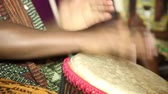 person playing on Jambe Drum no face. Closeup of mans hands drumming out a beat on an African skin-covered djembe hand drum.