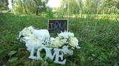 メートル : Wedding decoration word love , flowers and wooden plaque with the letters D and M on a background of green grass in the park