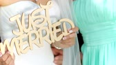 güvenilir : happy newlyweds holding a wooden placard Just married. wedding day Stok Video