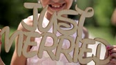 зуб : the little girl smiles and holds a wooden sign just merried.