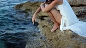 Beautiful girl in white dress is sitting on the beach. Greece