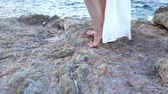 Beautiful girl in white dress is standing on the stones by the sea. Greece Stock Footage