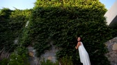 Beautiful girl on the background of a high stone wall with ivy