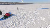 postroj : aerial view. Competitionspilots of the paraglider on a frozen lake near the city park. Winter sports. Winter fun