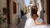delightful : happy cheerful bride runs along the street of the old city and looks back.