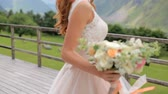 аккуратный : Beautiful red-haired bride dancing against the background of mountains Стоковые видеозаписи