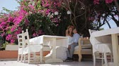 samimi : Beautiful and cheerful bride and groom are sitting in a summer cafe on the background of a blossoming tree