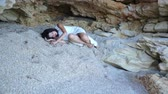 gruta : Frightened girl lies on the sand in a stone grotto and the tide of the sea approaches her Vídeos