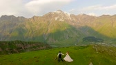 аккуратный : Newlyweds walk in the evening in the meadow against the backdrop of beautiful mountains. Concept - the whole world for lovers Стоковые видеозаписи
