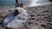 сюрреализм : Surrealism. Bride in a gorgeous dress with the groom are on the sand by the sea