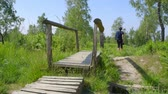 raised bog : Professional nature photographer, walking on a boardwalk - ProRes Stock Footage