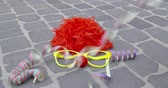 peruca : A funny wig, disguise glasses, a nose of foam material and streamers on a paved ground - carnival concept or celebration concept - ProRes