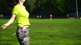 fitness : footage woman jumping on a skipping rope in a park close-up