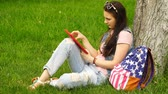 adult : footage young beautiful woman sitting near a tree on the grass in the park and use the app in your comuter tablet.