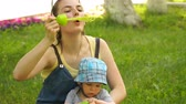 babies : footage woman with son blowing bubbles on nature