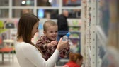 baby store : young mother and son buy water in a store or supermarket. Stock Footage