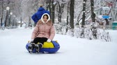 slide : young girl rolling on tubing in the park in winter. Stock Footage