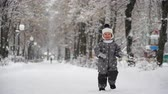 имеющий : boy of two years walks in the park in winter.