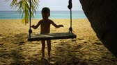 hinta : boy of two years swings on a swing on the beach near the ocean.